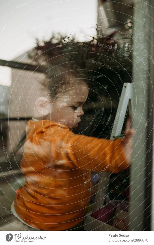 Kind durch Fenster durch Glas Isolation Quarantäne Quarantänezeit covid-19 sars-cov-2 im Innenbereich Coronavirus Prävention Pandemie Infektion Infektionsgefahr