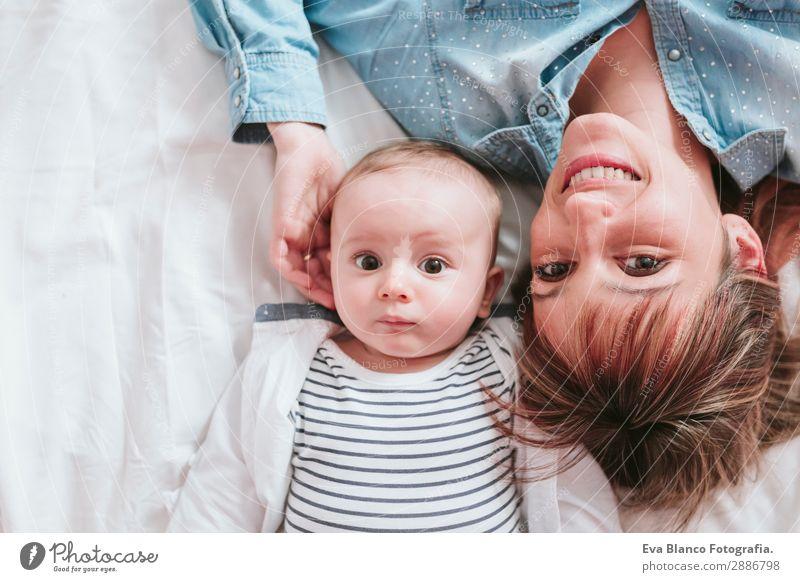 glückliche junge Mutter und ihr kleiner Junge liegen auf dem Bett und lächeln. Lifestyle Freude Glück Haut Lampe Schlafzimmer Kind Mensch maskulin feminin Baby