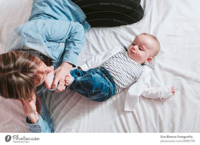 glückliche junge Mutter und ihr kleiner Junge liegen auf dem Bett und lächeln. Lifestyle Freude Glück Haut Lampe Schlafzimmer Kind Mensch feminin Baby Kleinkind