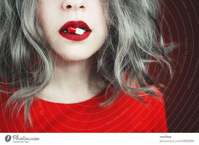 Nahaufnahme der Lippen junger Frauen, die eine Pille halten. Stil Design Haut Gesicht Lippenstift Gesundheitswesen Behandlung Rauschmittel Medikament Mensch