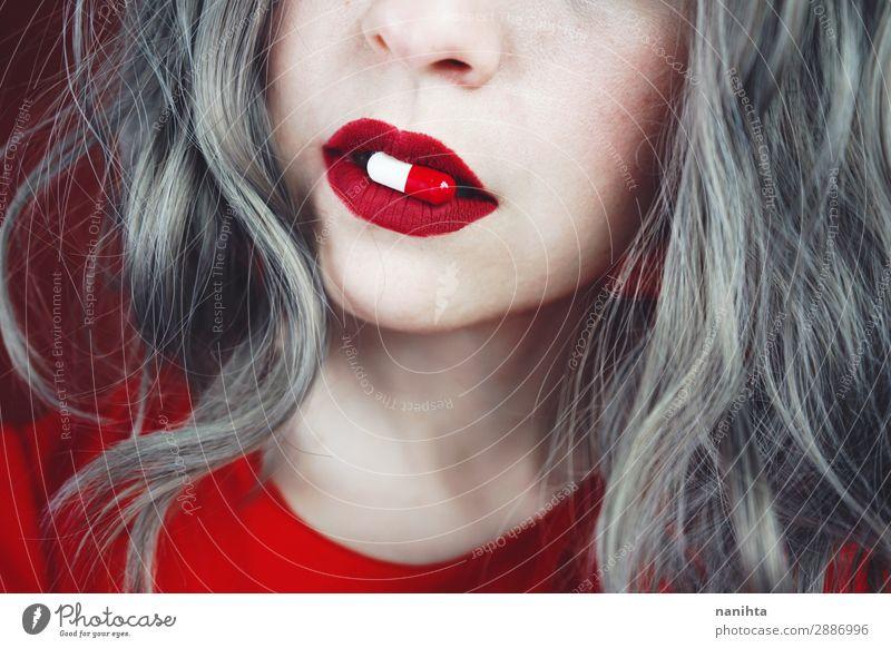 Nahaufnahme der Lippen junger Frauen, die eine Pille halten. Design Haut Gesicht Lippenstift Gesundheit Gesundheitswesen Behandlung Rauschmittel Medikament