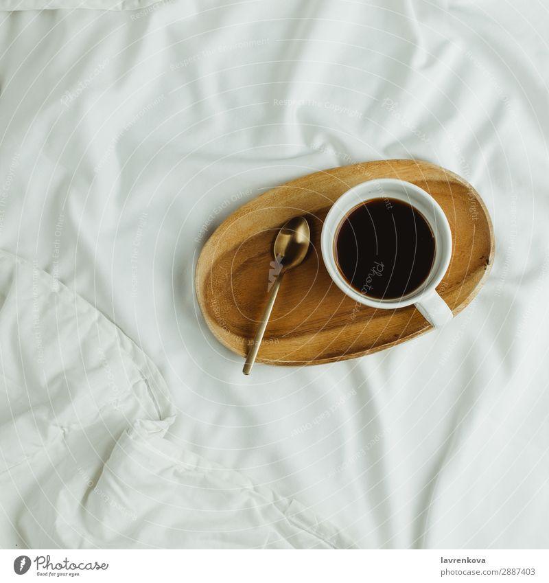 Tasse Kaffee und Löffel auf Holztablett im Bett auf weißen Laken Hintergrundbild Schlafzimmer Getränk schwarz Frühstück trinken Espresso Gesunde Ernährung