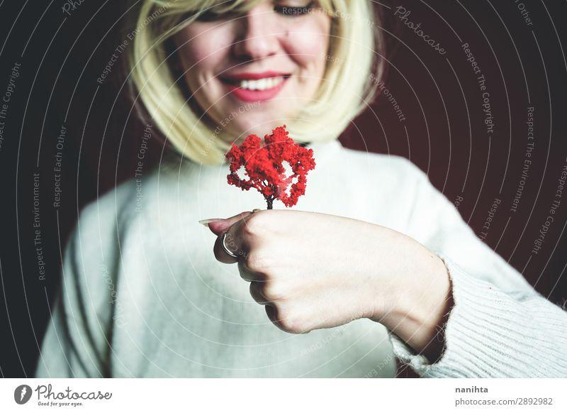 Junge Frau hält einen kleinen roten Baum. Design Mensch Erwachsene 1 Kunst Umwelt Natur Herbst Lächeln Wachstum authentisch einzigartig nachhaltig Schutz