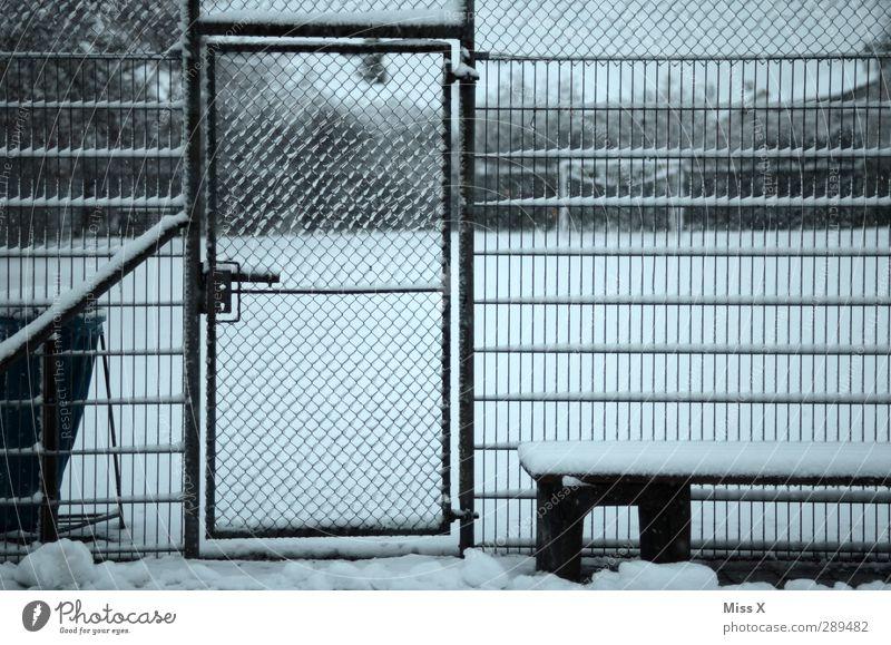 Winter Sportstätten Fußballplatz Rennbahn Schnee kalt trist grau Tür Metallzaun Maschendrahtzaun Gedeckte Farben Außenaufnahme Muster Menschenleer