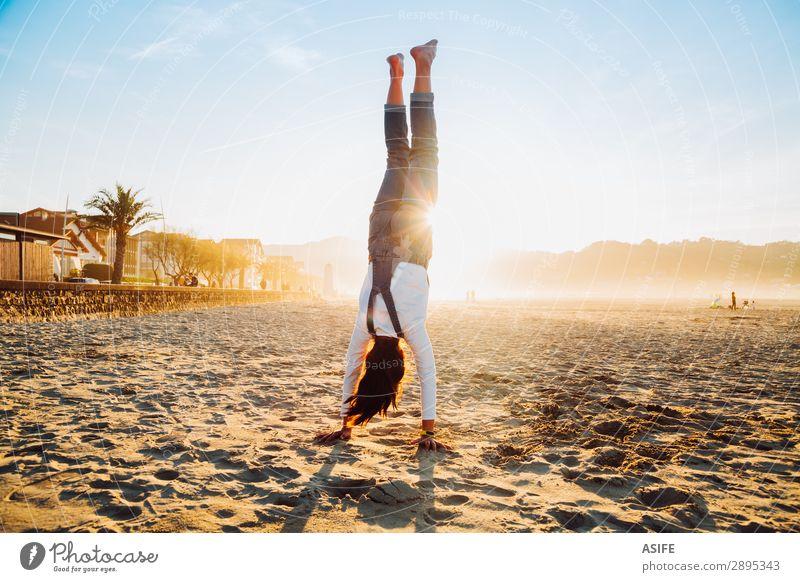 Kleines Mädchen steht auf Händen am Strand bei Sonnenuntergang. Freude Glück schön Spielen Ferien & Urlaub & Reisen Freiheit Sommer Meer Kind Natur Sand Himmel