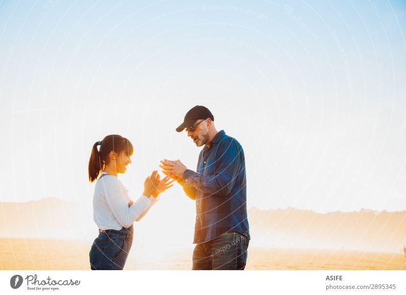 Vater und Tochter spielen am Strand bei Sonnenuntergang Handspiel. Freude Glück schön Spielen Kind Erwachsene Familie & Verwandtschaft Jeanshose Glatze Lächeln