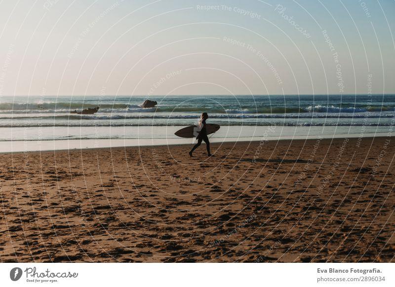 junger Surfer, der am Meeresufer entlanggeht. Lifestyle Freude Erholung Freizeit & Hobby Ferien & Urlaub & Reisen Tourismus Abenteuer Freiheit Sommer Strand