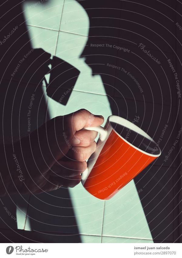 Hand mit Tasse Kaffee Finger Körperfett Innenaufnahme Frühstück Getränk trinken Halt Schatten Silhouette Lichterscheinung sehr wenige