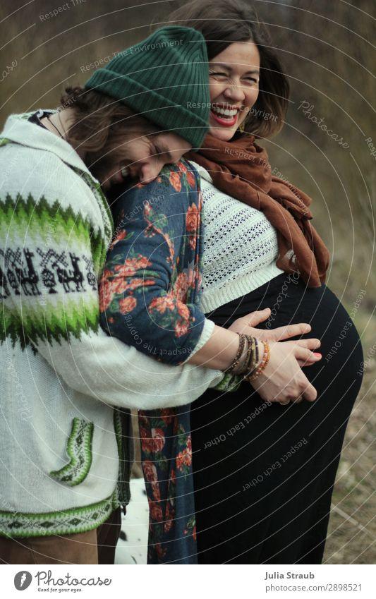 Hochschwangere Frau lacht und freut sich mit ihrem Mann Eltern Erwachsene Paar Partner 2 Mensch 30-45 Jahre Schal Mütze brünett langhaarig Vollbart berühren