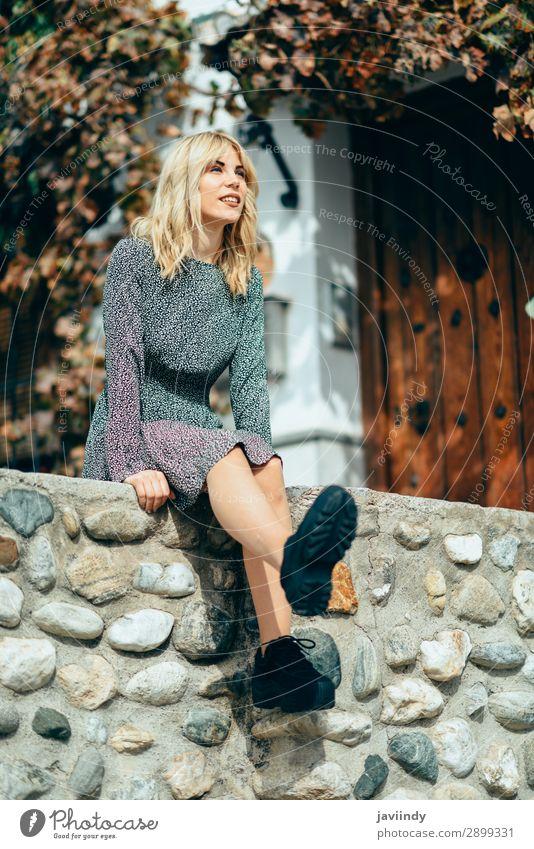 Glückliche junge blonde Frau, die auf dem urbanen Herbsthintergrund sitzt. Lifestyle Stil schön Haare & Frisuren Mensch feminin Junge Frau Jugendliche