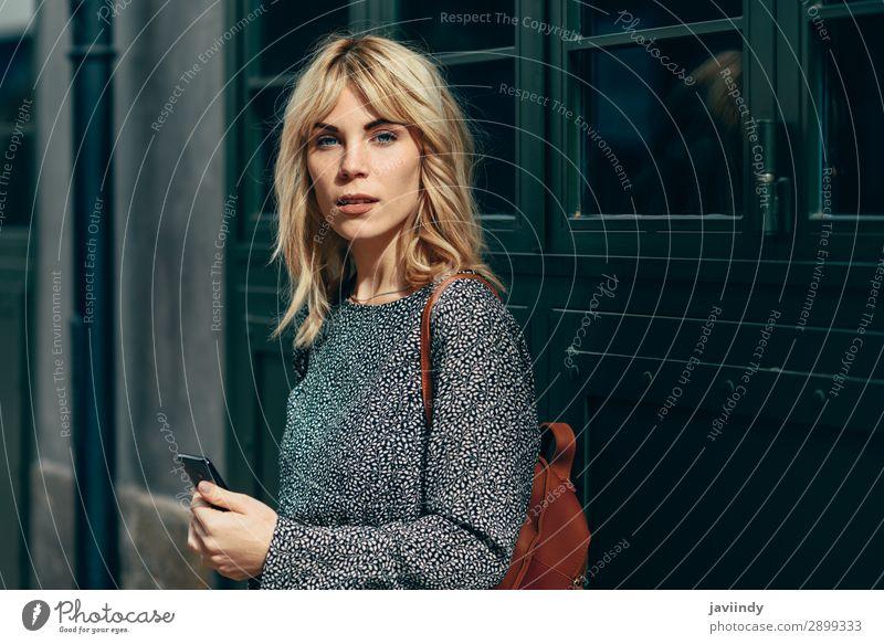 Junge kaukasische Frau schaut auf ihr Smartphone im Freien. Lifestyle Stil schön Haare & Frisuren Telefon PDA Mensch Erwachsene Herbst Straße Mode Bekleidung