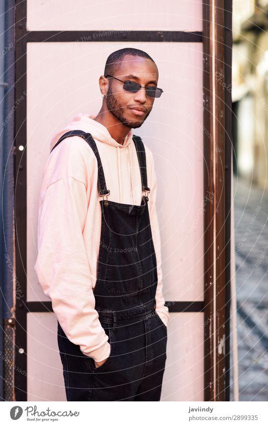 Afrikanischer Typ mit Latzhose, die im Freien steht. Lifestyle schön Mensch maskulin Junger Mann Jugendliche Erwachsene 1 18-30 Jahre Straße Mode Bekleidung