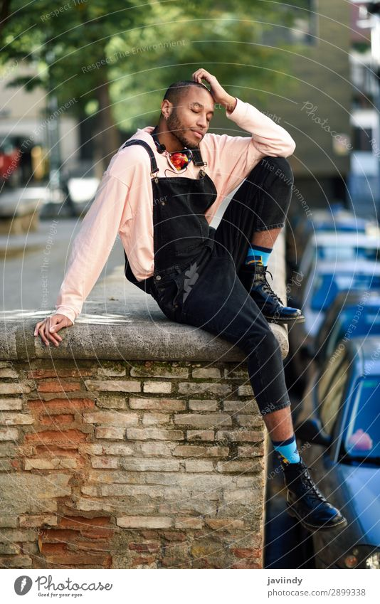 Fröhlicher afrikanischer Typ mit Latzhose im Freien Lifestyle Glück schön Mensch maskulin Junger Mann Jugendliche Erwachsene 1 18-30 Jahre Straße Mode