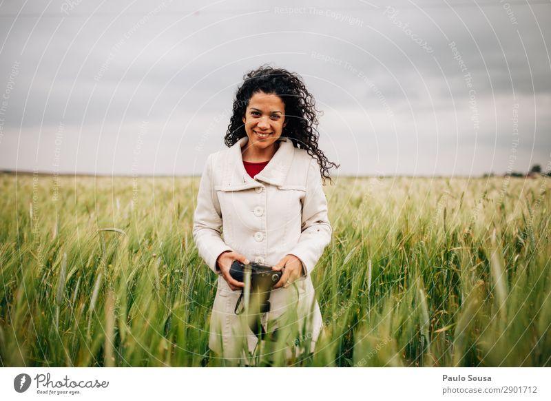 Mädchen mit Kamera lächelnd auf Feldern Lifestyle Fotografie Ferien & Urlaub & Reisen Frühling Fotokamera Junge Frau Jugendliche Erwachsene 1 Mensch 18-30 Jahre
