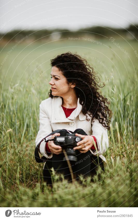 Mädchen, das mit einer Kamera auf Feldern sitzt. Lifestyle Fotografie Ferien & Urlaub & Reisen Ausflug Abenteuer Frühling Fotokamera feminin Junge Frau