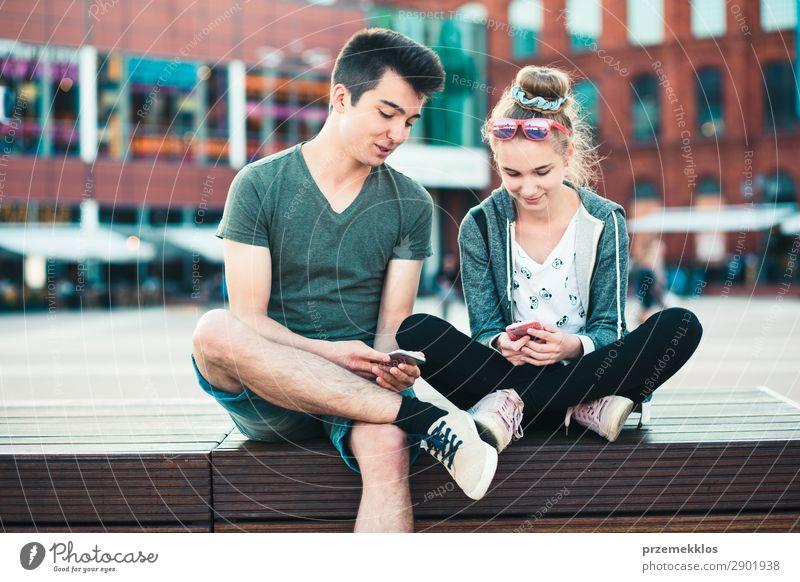 Ein paar Freunde, die zusammen mit Smartphones Spaß haben. Lifestyle Sommer sprechen Telefon Handy PDA Technik & Technologie Frau Erwachsene Mann Freundschaft