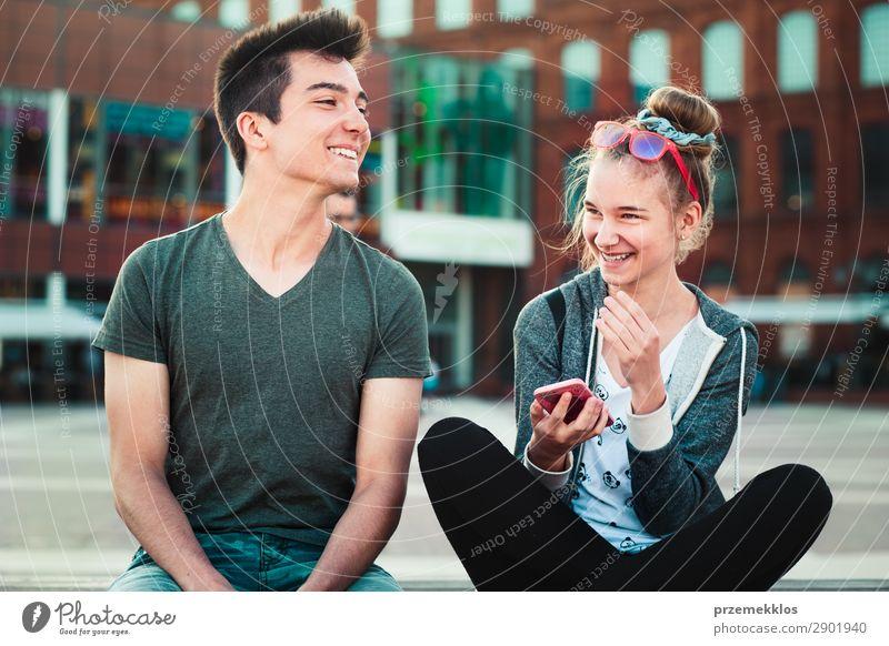Ein befreundetes Paar, ein Mädchen und ein Junge im Teenageralter, die sich gemeinsam mit Smartphones amüsieren, im Stadtzentrum sitzen und Zeit miteinander verbringen