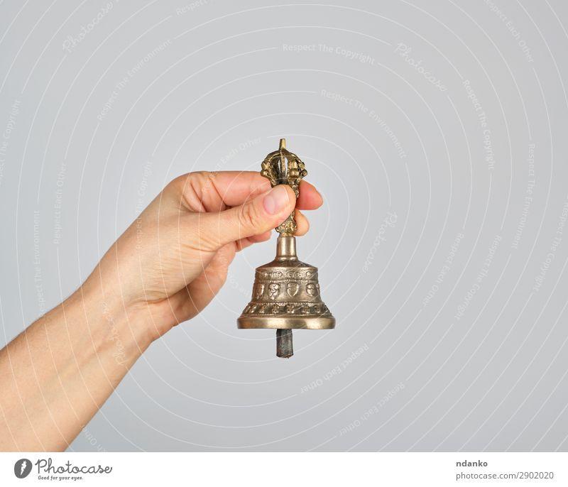 weibliche Hand mit einer Bronzeglocke für die Alternativmedizin Lifestyle harmonisch Erholung Meditation Yoga Metall alt braun grau Gesundheitswesen