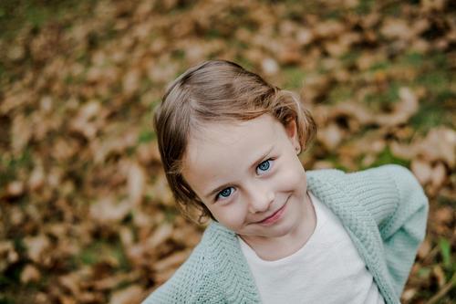 Lächelndes Mädchen zwischen den Wiesen mit trockenen Blättern Blatt regenarm Kind positiv Feld