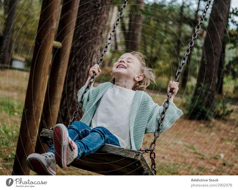 Lächelndes Mädchen auf Schaukeln im Park Wald Kind positiv Baum Natur schön Frau Kindheit Freiheit Freude Holz Lifestyle heiter Mode Garten Freizeit & Hobby