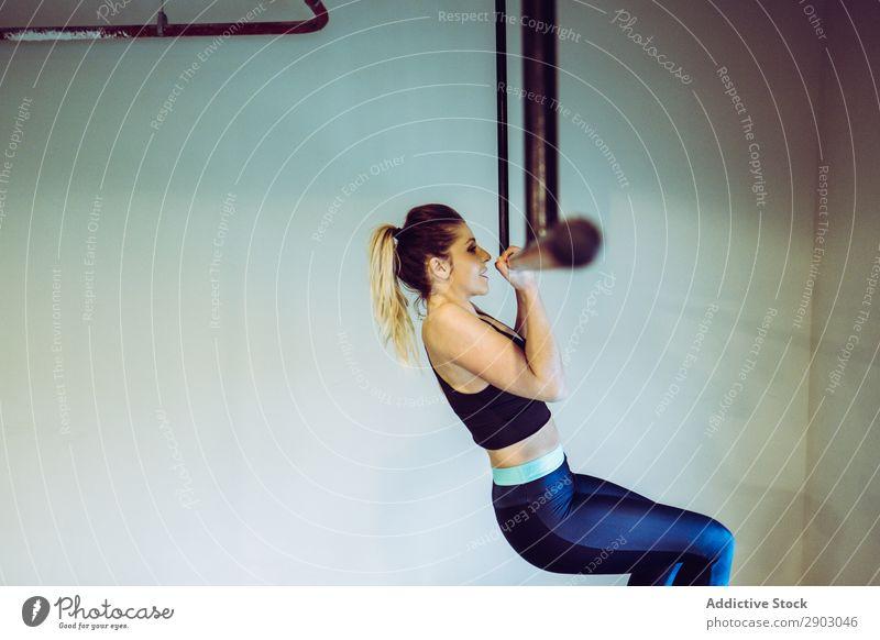 Junge Frau, die Pull-Ups im Fitnessstudio macht. Klimmzüge Bar Sporthalle aufschauend Training üben Athlet stark Gesundheit Aktion physisch muskulös
