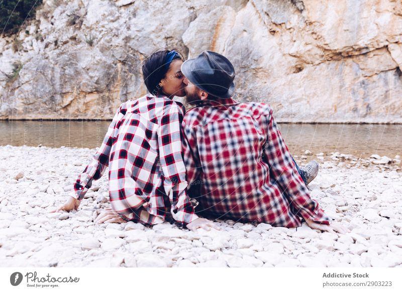 Positive Frau und Mann ruhen und küssen sich auf dem Steinufer am Fluss. Paar Berge u. Gebirge Felsen positiv Lächeln