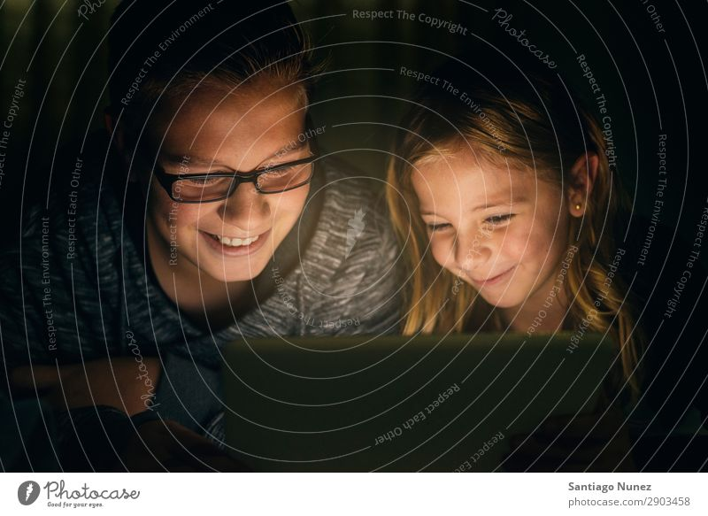 Zwei süße Kinder, die auf einem Tablet PC spielen. Tablet Computer Lächeln Spielen Mädchen Junge klein Zusammensein digital heimwärts 2 Glück Brillenträger