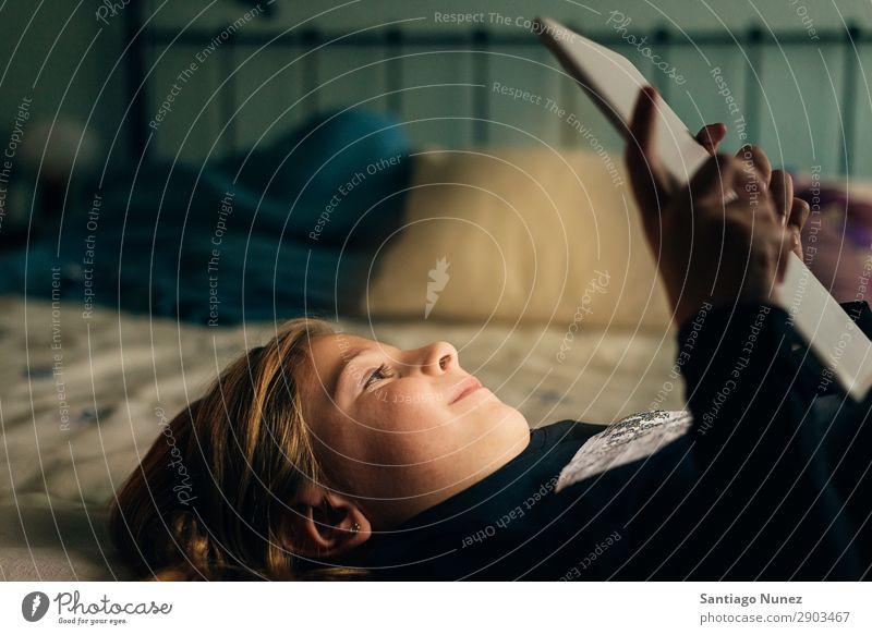 Süßes blondes Mädchen, das auf einem Tablet spielt. Tablet Computer Kind Lächeln Spielen klein digital heimwärts Glück Etage Mensch Technik & Technologie Freude