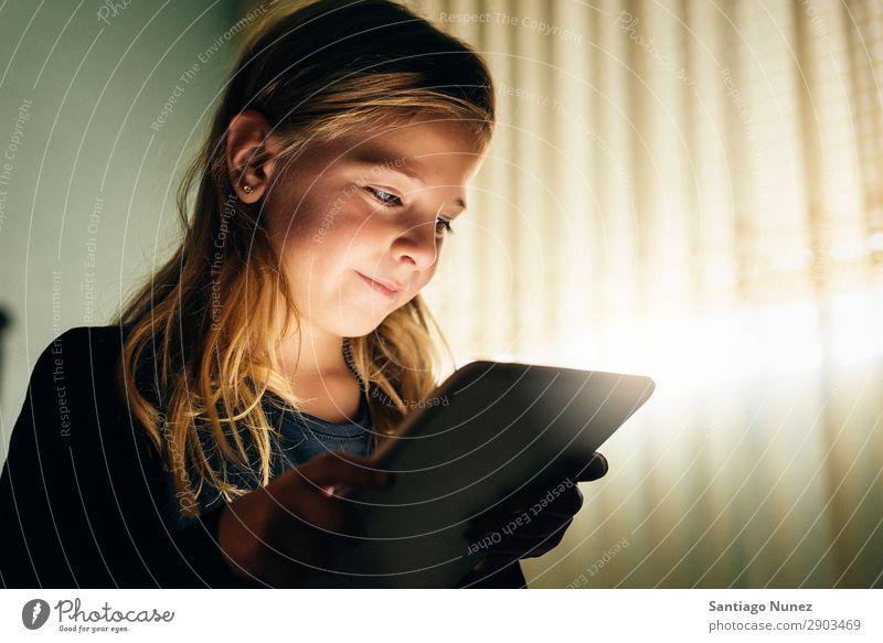 Süßes blondes Mädchen, das auf einem Tablet PC spielt. Tablet Computer Kind Lächeln Spielen klein digital heimwärts Glück Etage Mensch Technik & Technologie