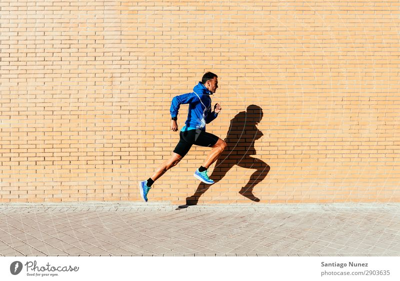 Ein gutaussehender Mann, der in der Stadt herumläuft. rennen Joggen Läufer Straße Großstadt Athlet Geschwindigkeit Fitness Lifestyle Jugendliche Aktion Schatten