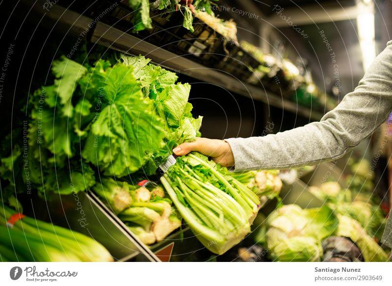 Nahaufnahme einer Frau, die im Supermarkt einen Salat nimmt. kaufen Hand nehmen Lebensmittel Markt benutzend Mensch Jugendliche Lächeln Karre Lifestyle Kunde