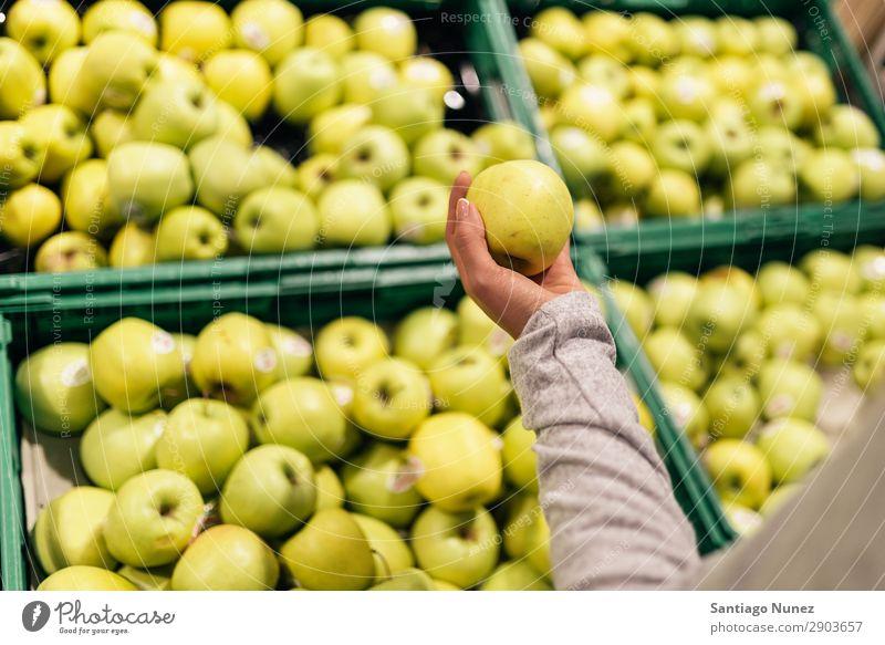 Schöne Frau, die Äpfel im Supermarkt auswählt. Frucht Nahaufnahme Lager Mensch Apfel Markt auserwählend Lebensmittel Hand Gesundheit frisch Halt kaufen