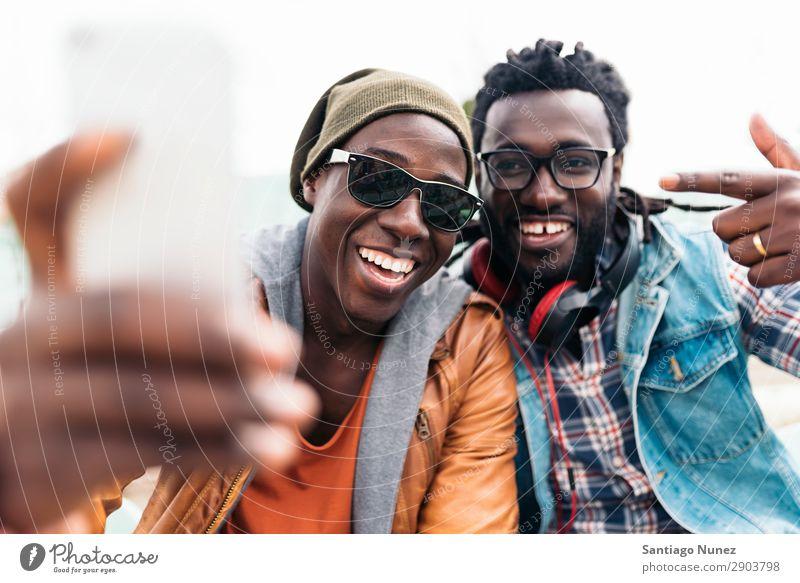 Zwei schwarze Rassenfreunde, die Spaß haben. Freundschaft Telefon Handy Stadt Afrikanisch Amerikaner Mobile Jugendliche Mann lachen PDA Technik & Technologie