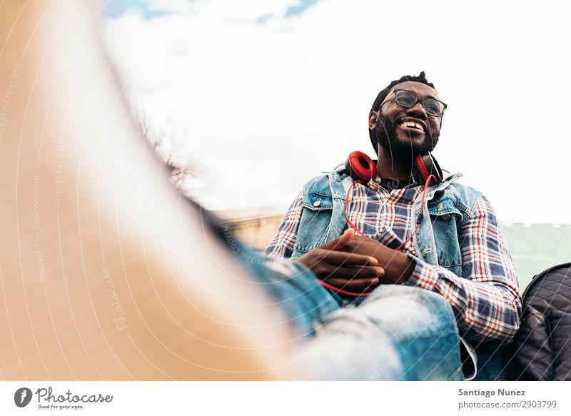 Afrikanischer junger Mann beim Musikhören. Kopfhörer Lifestyle schwarz Amerikaner Stadt Porträt Telefon PDA Mobile Solarzelle gutaussehend Technik & Technologie