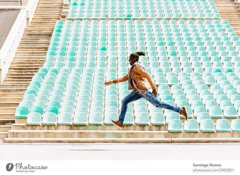 Ein amerikanischer Mann, der in den Park springt. Telefon Stadt springen handelnd Afrikanisch schwarz Amerikaner Jugendliche Mensch Glück Fröhlichkeit Lächeln