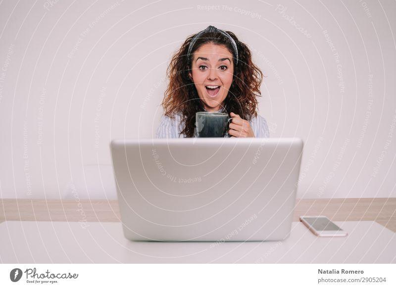 Junge Frau mit einem Becher in der Hand schaut überrascht auf ihren Laptop. Kaffee Lifestyle Glück Schreibtisch Tisch Arbeit & Erwerbstätigkeit Büro Business