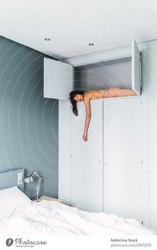 Frau im Schrank liegend im Schlafzimmer lügen Regal Entwurf Bett Jugendliche Wahnsinn Höhe Somnambulismus Bekleidung schlafen träumen brünett Innenarchitektur