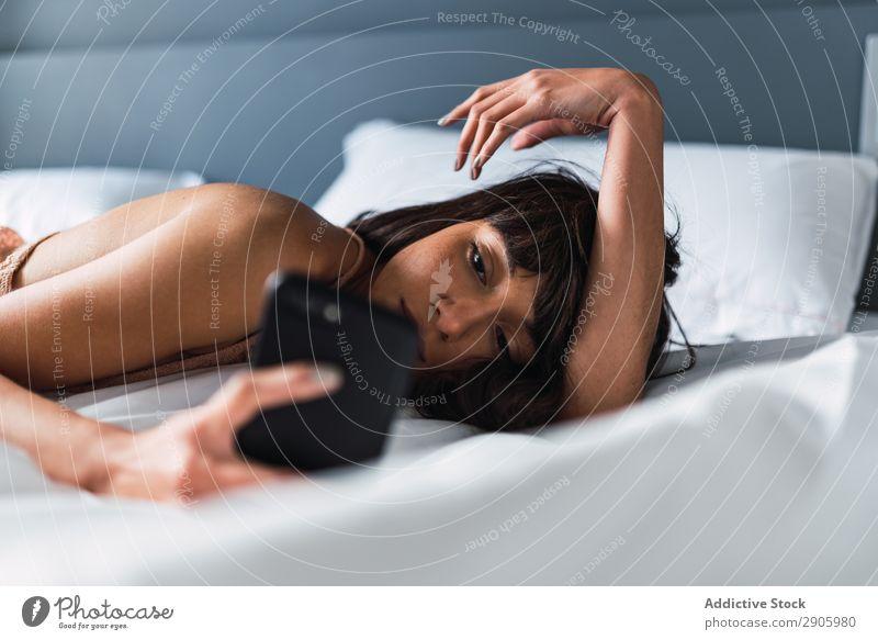 Frau mit Smartphone auf dem Bett liegend PDA Schlafzimmer heimwärts lügen benutzend aussruhen Handy Jugendliche Internet Mitteilung attraktiv Erholung Raum