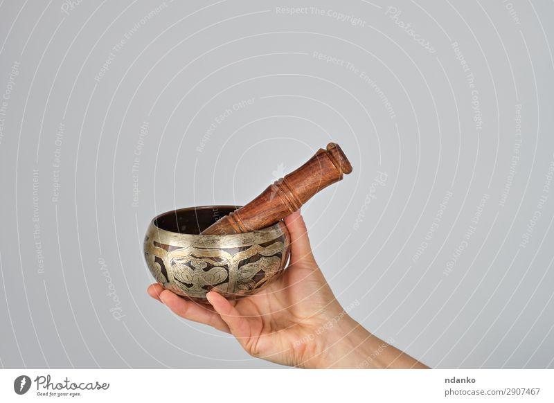 Kupferklangschale und Holzstab in Frauenhand Schalen & Schüsseln Lifestyle Körper Erholung Meditation Musik Yoga Erwachsene Hand Metall weiß Frieden