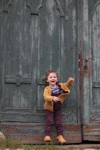 Tor Mädchen hüpfen feminin Kleinkind 1 Mensch 1-3 Jahre Tür Latzhose Strickjacke brünett kurzhaarig Pony Dutt Bewegung lachen springen frech frei Fröhlichkeit