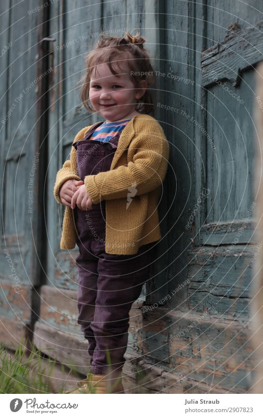 Mädchen alte Tür Holz feminin Kleinkind 1 Mensch 1-3 Jahre Gebäude Latzhose Strickjacke brünett kurzhaarig Pony Zopf Lächeln Scham verlegen Holztor abblättern