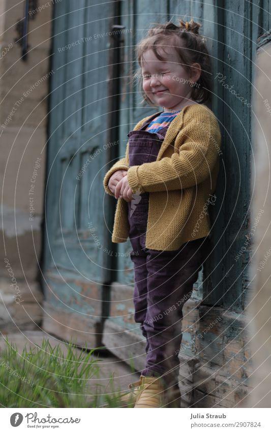 Mädchen Augen zwinkern Tor feminin Kleinkind 1 Mensch 1-3 Jahre Gras Königsberg Tür Strickjacke Latzhose Stiefel brünett kurzhaarig Pony Dutt klein verstecken