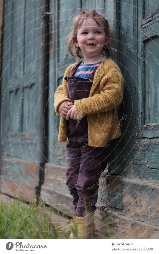 kleines Mädchen steht an petrol blauen alten Holztor und lacht feminin Kleinkind 1 Mensch 1-3 Jahre Altstadt Tor Tür Strickjacke Latzhose brünett kurzhaarig
