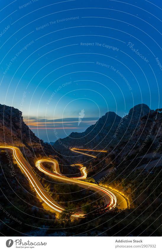lange Expositionsstraße bei Nacht zwischen den Bergen Geschwindigkeit rot Licht Verkehr Bewegung Straße Belichtung Szene Weg Farbe Ferien & Urlaub & Reisen