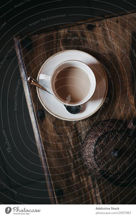 Tasse Tee auf dem Tisch Milch Teekanne frisch Untertasse Löffel trinken gebraut dunkel Raum gemütlich heiß Wärme Gesundheit Vorbereitung Portion Frühstück