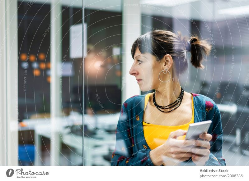 Frau beim Surfen auf dem Smartphone im Büro benutzend PDA Glas Wand Lächeln Erwachsene modern Pause Mobile Telefon Technik & Technologie Gerät Apparatur Browsen