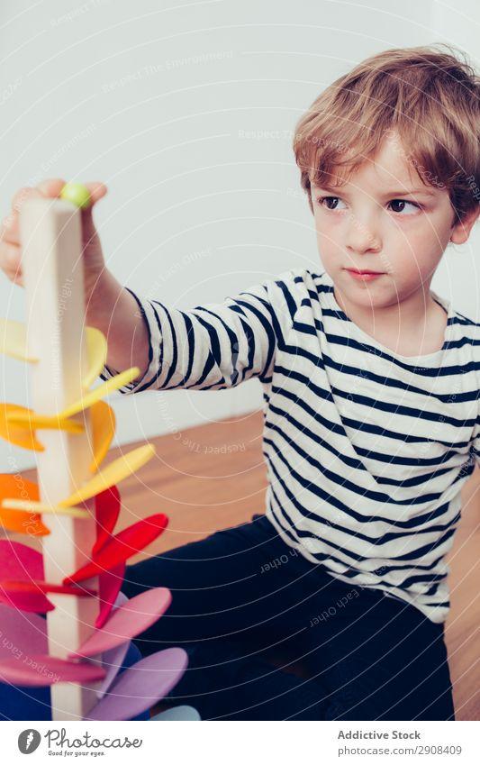 Junge spielt mit Holzbauteilen Aktion blond bauen Kind Kindheit Kreativität niedlich Bildung genießen Freude Glück heimwärts im Innenbereich Marmor montessori