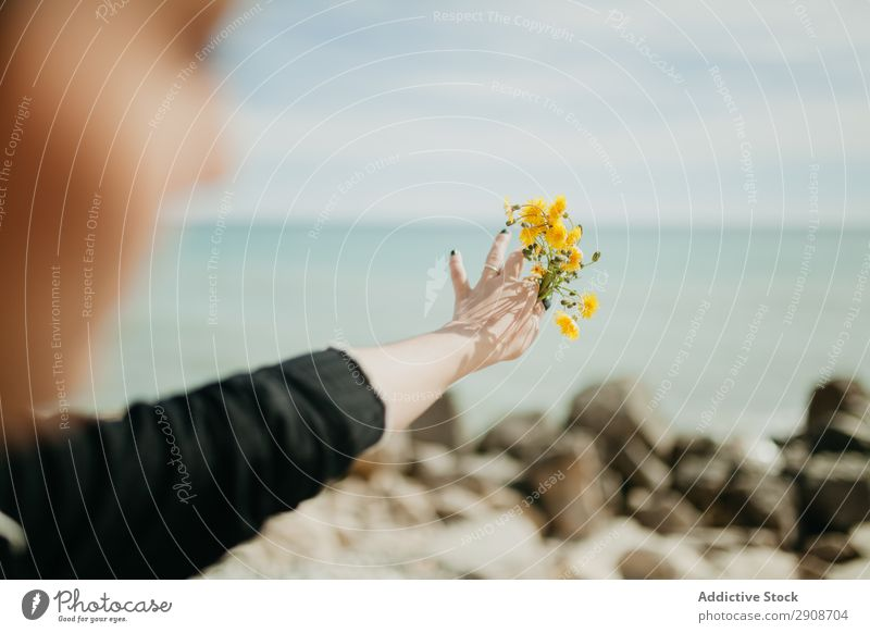 Anonyme Frau, die Blumen ins Meer wirft. Klippe Resort Sonnenstrahlen Tag Jugendliche