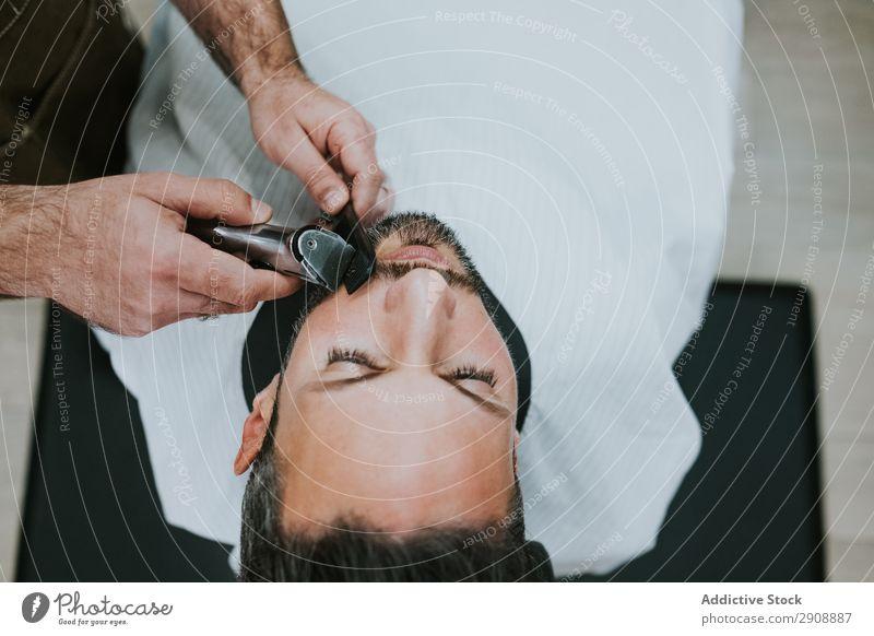 Barbier schneidet Bart zu Mann im Salon Friseursalon Schneiden Vollbart Hand Trimmer Kamm Stil professionell sitzen Mode Lifestyle Erwachsene Reichtum Kunde