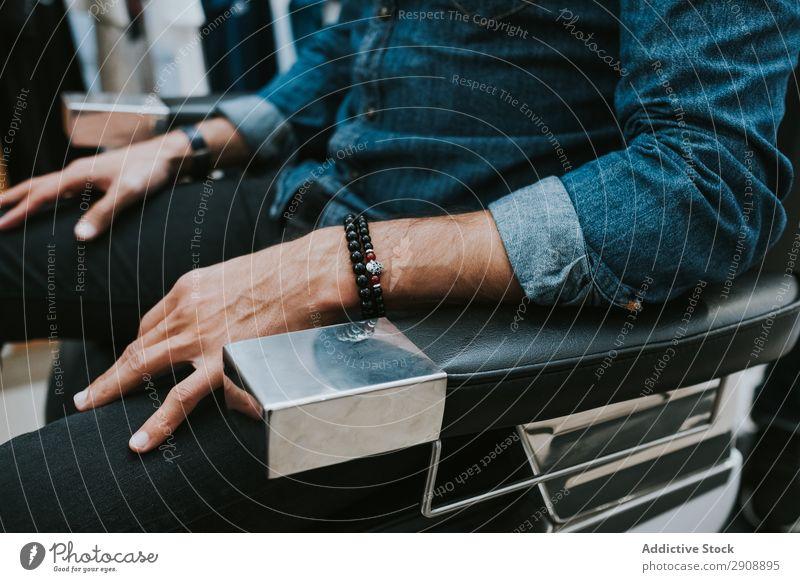 Mann im Stuhl im Salon sitzend Stil Jugendliche Armband Hand Friseur Fürsorge Friseursalon Haare & Frisuren Mode maskulin Studioaufnahme professionell Reichtum